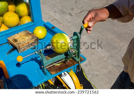street vendor in Mexico peeling orange for juicing  - stock photo