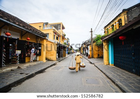 Street vendor with shoulder pole and conical hat in Hoi An Ancient Town, Quang Nam, Vietnam. Hoi An is recognized as a World Heritage Site by UNESCO. - stock photo