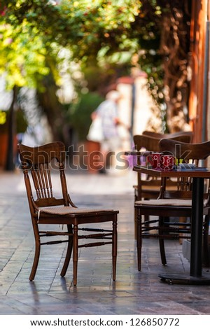 Street view of a empty coffee terrace with tables and chairs in old town of Antalya, Turkey. Small depth of field. - stock photo