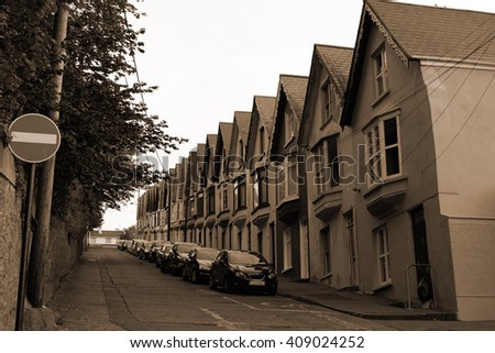 street view of houses on a steep hill in cobh county cork ireland in sepia - stock photo