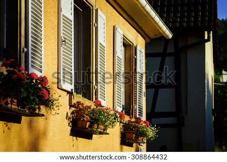 Street view of old windows with shutters, Andlau, France, Alsace - stock photo