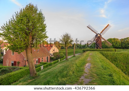 Street view with houses, dike and mill in the renovated historic fortress town of Bourtange in Groningen, the Netherlands. - stock photo