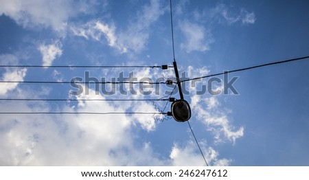 Street wires with a lamp against a sky background