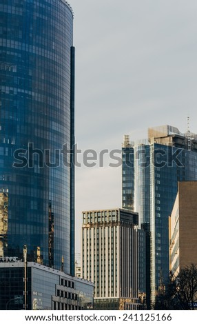Street with facades of skyscrapers on a cloudy day - stock photo