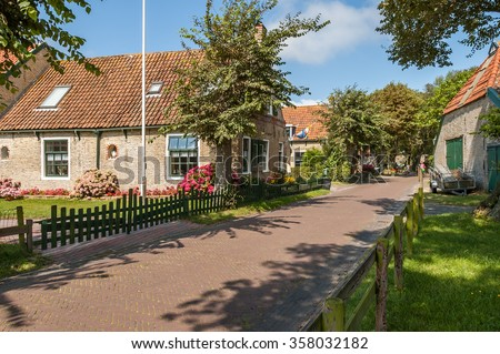 Street with old Dutch commander houses in the town of Hollum on the West-Frisian island Ameland, Netherlands - stock photo