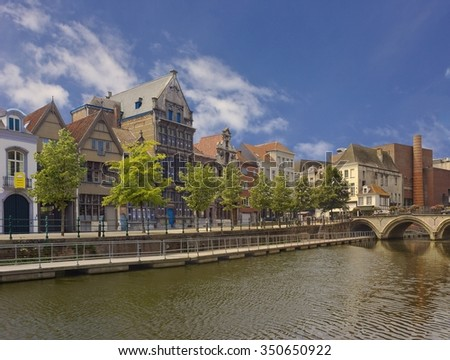 Street with old historical buildings on the river bank in Mechelen, Belgium with water on the foreground and old bridge on the background