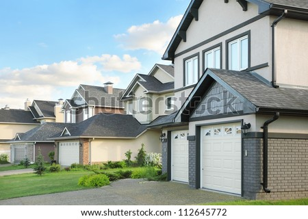 Street with two-storied brown cottages with built-in garage. Green grass near houses. - stock photo