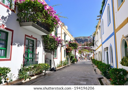 Street with white houses colonia shown in Puerto de Mogan, Spain.  Favorite vacation place for tourists and locals on island. - stock photo