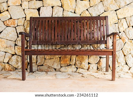 Street wooden bench against brick wall. - stock photo