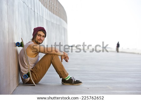 Streetwise youth, sitting carefree against the granite wall of a boardwalk looking difiantly into the camera, with his skateboard next to him - stock photo
