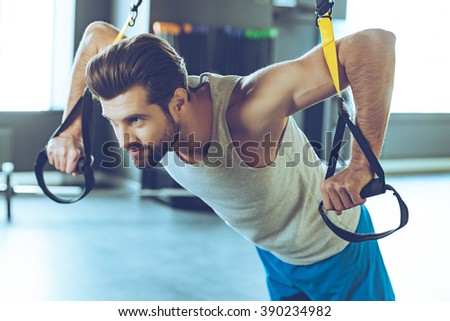 Strength and concentration. Young handsome man in sportswear exercising at gym - stock photo