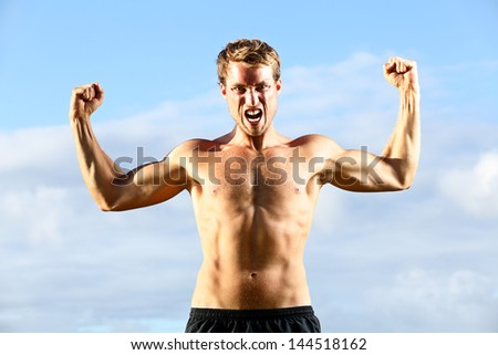 Strength - strong aggressive fitness man flexing muscles showing power pose outside. Muscular fit male fitness man celebrating success macho style.