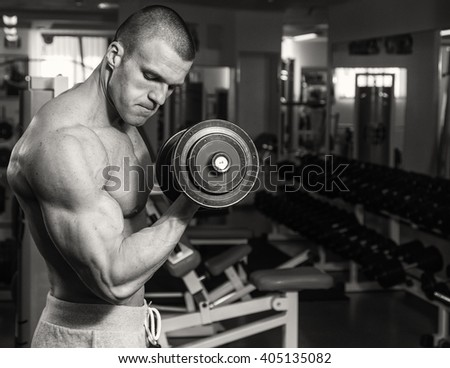 Strength training with dumbbells. Husky holds a large dumbbell in hand. Sport, bodybuilding, healthy lifestyle.