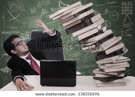 Stress businessman with falling books and laptop at classroom - stock photo
