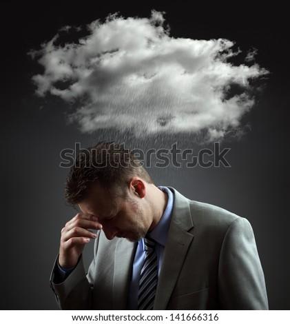 Stress, depression and despair - gloomy storm cloud raining above a businesmans head - stock photo