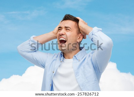 stress, headache, health care and people concept - unhappy man with closed eyes touching his forehead over blue sky and cloud background - stock photo