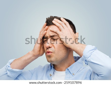 stress, headache, health care and people concept - unhappy man with closed eyes touching his forehead over gray background - stock photo