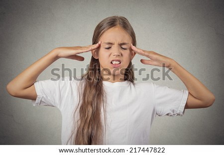 Stress. Portrait stressed teenager girl hands on temples, head spinning around, overwhelmed at school in life,isolated grey wall background. Negative human facial expression emotion feeling perception - stock photo