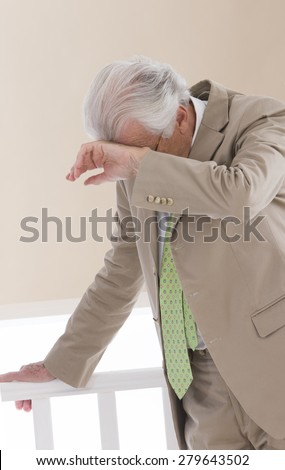 Stressed and overworked- Senior business man having discomfort and holding on to the banister - stock photo