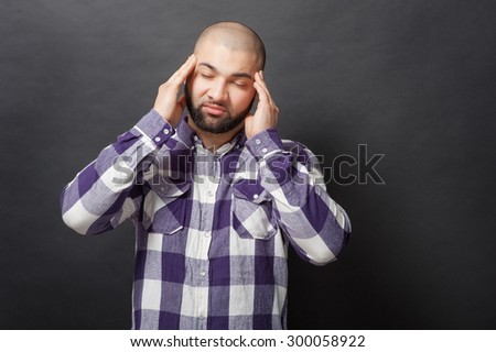 Stressed and tired. Sad young bearded man holding hands on his head with eyes closed while standing against black background.