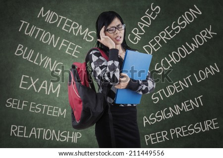Stressed asian student having many problems and feel dizzy  in a classroom - stock photo