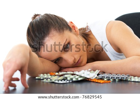 stressed attractive young brunette holds some pills, isolated