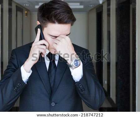 Stressed business man on his cellphone - stock photo