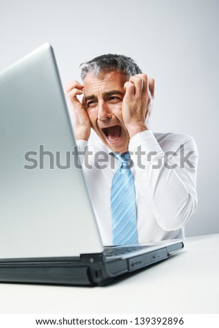 Stressed business man sitting at his desk, panics in front of his computer - stock photo