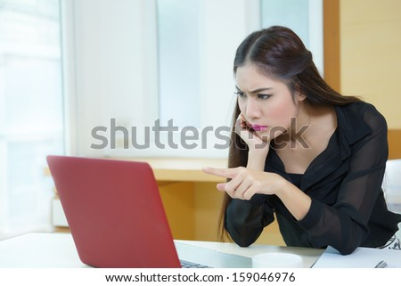 Stressed business woman is frustrated and point to screen. Model is Asian woman.  - stock photo