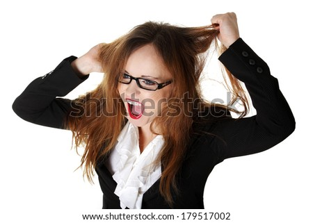 Stressed business woman is going crazy pulling her hair in frustration. - stock photo