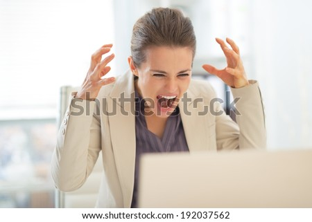 Stressed business woman with laptop at work - stock photo