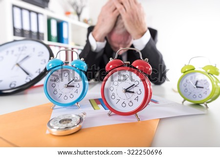 Stressed businessman behind  his desk full of alarm clocks