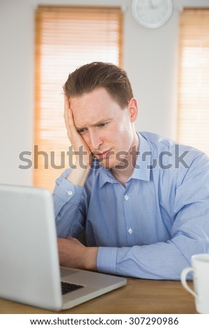 Stressed businessman looking at his laptop in the office