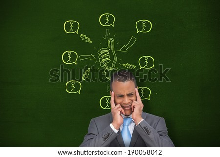 Stressed businessman putting his fingers on his temples against green - stock photo