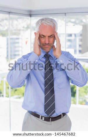 Stressed businessman rubbing his temples with eyes closed standing in his office - stock photo