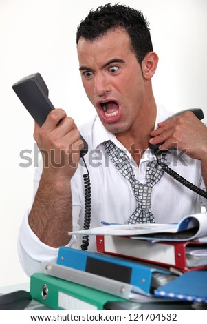 Stressed businessman screaming at a phone - stock photo