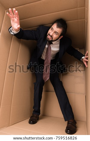 stressed businessman standing in cardboard box