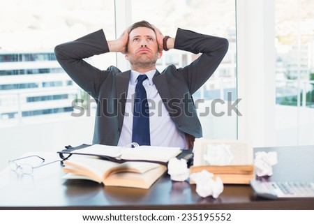 Stressed businessman taking his head in his office - stock photo