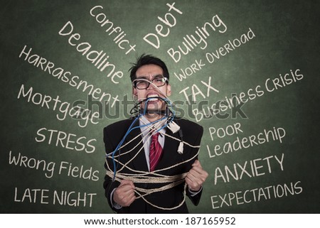 Stressed businessman tied with a rope at classroom - stock photo
