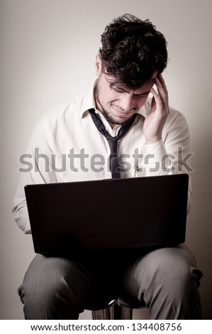 stressed businessman using notebook on gray background