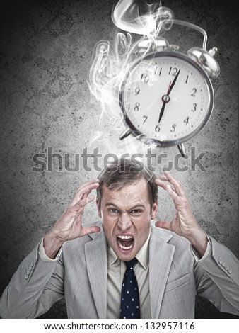 Stressed businessman with a deadline on grey background - stock photo