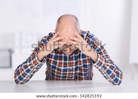 Stressed businessman with head in hands sitting at desk in office - stock photo