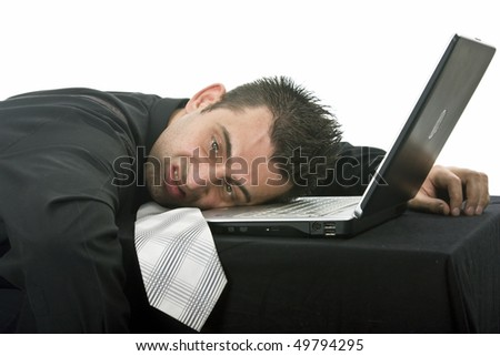 Stressed businessman with his head resting on the laptop computer keyboard. - stock photo