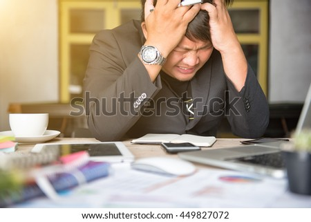 Stressed businessman Worried businessman in dark suit sitting at office desk full with books and papers being overloaded with work. - stock photo