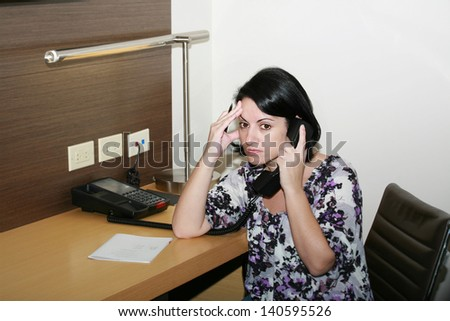 Stressed businesswoman holding her forehead while speaking on the telephone - stock photo