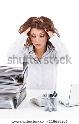 Stressed businesswoman is overworked at her desk - stock photo