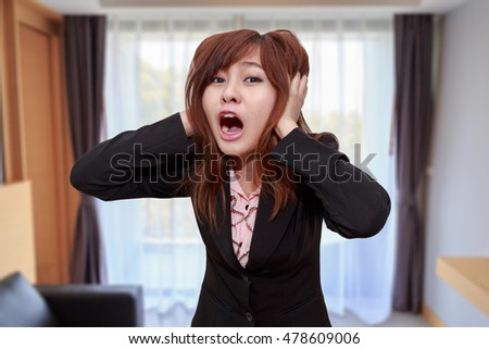 Stressed businesswoman shocked or screaming while holding her head in office - Business concept