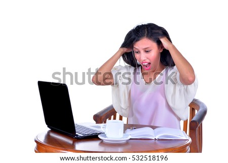 Stressed businesswoman shouting loudly at laptop