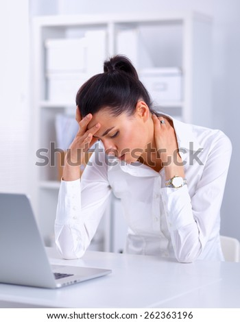 Stressed businesswoman sitting at desk, isolated on white