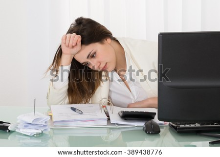 Stressed Businesswoman Sitting In Office With Hand On Head